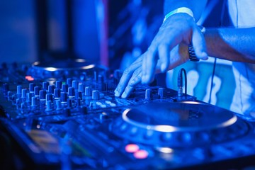 dj-playing-music-at-mixer-on-colorful-blurred-PAZNFQ5.jpg